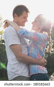 Side view of a smiling young couple looking at each other against the sky