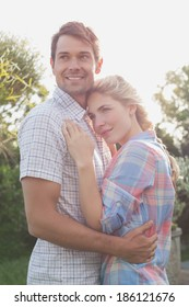 Side view of a smiling young couple embracing in the park