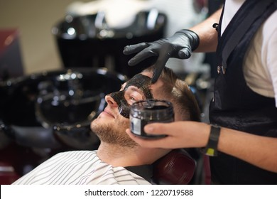 Side view of smiling young man lying on chair in vintage barber shop while barber in protective gloves putting black mask against dots on face. Concept of skin care and cleaning.