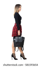 Side view of smiling young stylish street style woman carrying bag walking and looking up. Full body length isolated over white studio background.