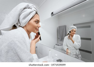 Side view of smiling young woman in robe and towel doing makeup after shower at home or hotel. Concept of process preparing skin for makeup in modern bathroom.