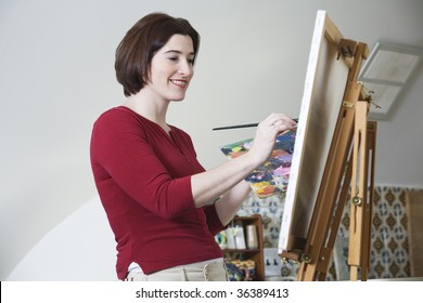 Side view of a smiling young woman painting.