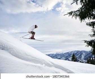 Side view snapshot of skier conducting extreme jump from a snowy slope, flying against amazing sky and mountain range on background. Copy space. Concept of skiing and winter sport activities. - Shutterstock ID 1807345366