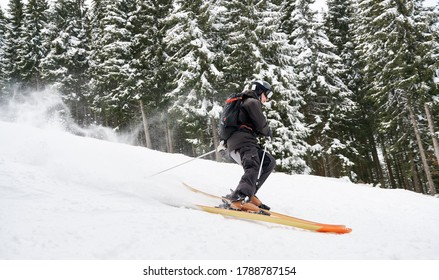 Side view snapshot of skier skiing down the piste along spruce forest. Keeping balance on snow. Concept of extreme winter kinds of sport. Season entertainment