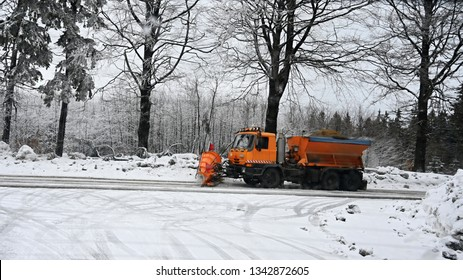 Side view of snowplow service truck - gritter car spreading salt on the road. Maintenance of roads in winter in the mountains.