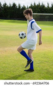 Side view of soccer player playing with ball on field