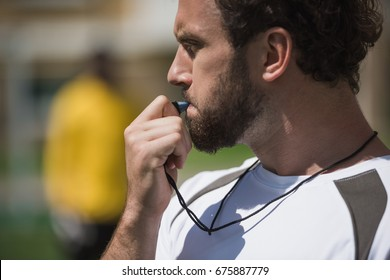 side view of soccer referee whistling in whistle on soccer pitch during game
