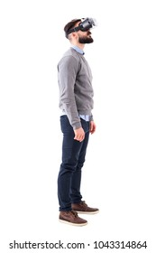 Side view of speechless young man having virtual reality glasses experience looking up above. Full body portrait isolated on white background.
