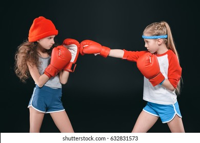 side view of sportive girls pretending boxing isolated on black, active kids concept