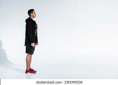 side view of sportive mixed race man in black sportswear and red sneakers on white background with copy space
