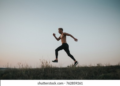 Side view of sportive shirtless man in motion of running on hill in dusk