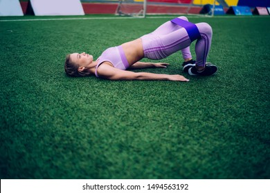 Side view of sportive young female in active wear lying on football field and doing glute bridge with fitness band on hips