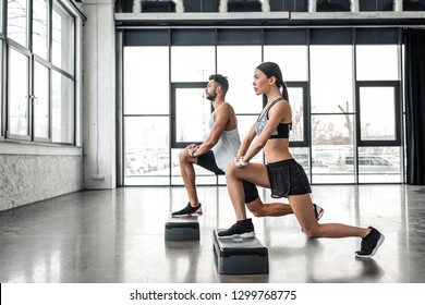 side view of sportive young man and woman training with step platforms in gym