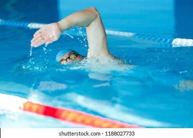 Side view of sports man in blue cap floating on path in pool