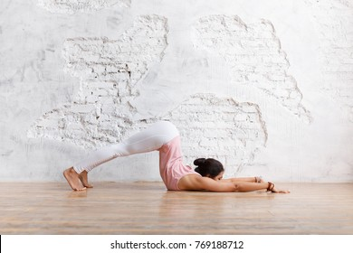 Side view - sports unidentified young woman doing complex yoga exercise stretching her legs and arms in the gym on white wall background. Copy space