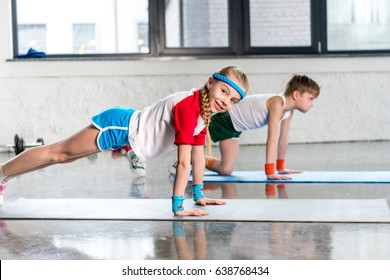 Side view of sporty boy and girl in sportswear doing push ups in gym, children sport school concept
