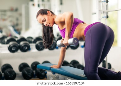 Side view of sporty lady with well-shaped body doing exercise with dumbbell in gym. Beautiful athletic girl in sport crop top and leggings lifting weight. Concept of sport.