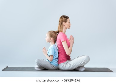 Side view of sporty mother and daughter practicing lotus yoga pose and namaste gesture together isolated on grey