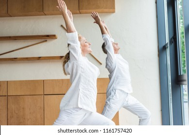 Side view of sporty senior couple performing warrior pose while practicing yoga at home