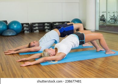 Side view of a sporty young couple doing pilate exercises at fitness studio