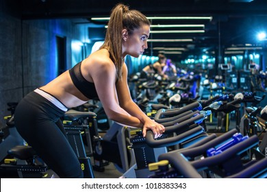 Side view of sporty young woman riding on exercise bike in gym.