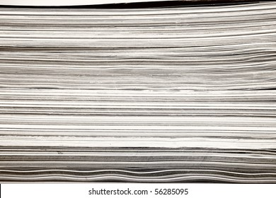 Side view of stack of papers, books, and magazines for recycling.