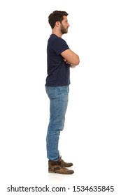 Side view of standing man with arms crossed and looking away. Side view. Full length studio shot isolated on white.