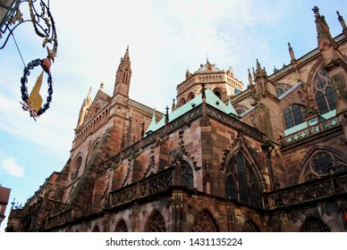 Side view of Strasbourg Cathedral or the Cathedral of Our Lady of Strasbourg also known as Strasbourg Minster, is a Catholic cathedral in Strasbourg, Alsace, France. Along with ornate church sign.