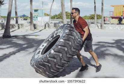 Side view of strong athletic man in sunglasses and sportswear pushing huge heavy tyre in bright sunlight on sandy beach.