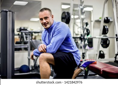 Side view of strong fitness trainer, inside room of a luxury gym, heavy exercise tools near wall, a body builder standing on a bench, he is smilling.