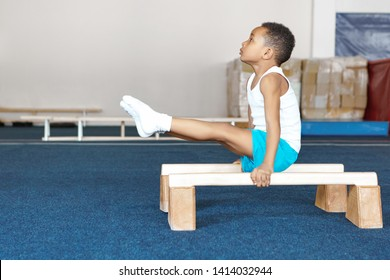 Side view of strong flexible dark skinned male child in sportswear doing exercises on wooden parallel bars, balancing body upright with arms straight, raising legs. Strength, flexibility and endurance