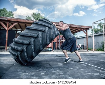 Side view of strong muscular fitness man moving large tire in street gym. Concept lifting, workout training