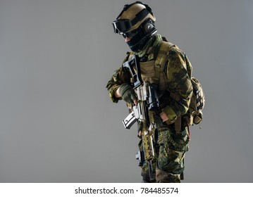 Side view strong soldier holding weapon in arms. War concept. Copy space. Isolated