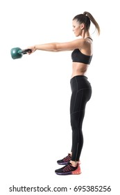 Side view of strong sporty fitness woman swinging 12 kg kettlebell in mid air motion. Full body length portrait isolated on white studio background
