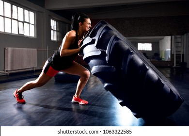 Side view of strong woman pushing tire during workout, flipping big wheel truck exercises