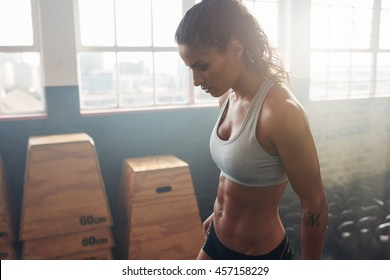 Side view of strong woman standing in the gym. Fitness female taking a break from intense workout.