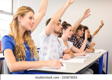 Side view of students raising hands in classroom