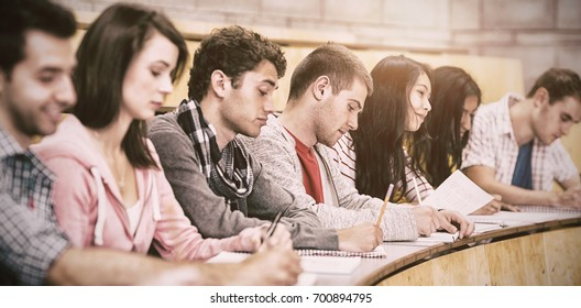 Side view of students writing notes in row at college lecture hall
