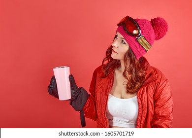 Side view studio shot portrait woman wearing rad ski clothes and standing in red background with tinsel and ski mask