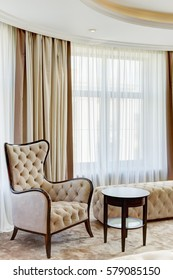 Side view of stylish armchair in classic style and rounded wooden table near. Light living room with big window on background, curtain in beige and brown colors.