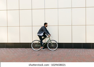 Side view of a stylish bearded man riding a bicycle on the city street.