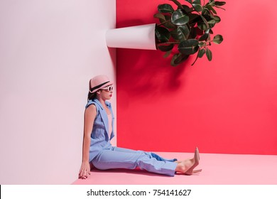 side view of stylish girl in hat and sunglasses sitting upside down in studio