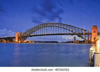 Side view of Sydney Harbour bridge against blue water and sunsettign sky with full illumination of metal arch and Kirribilli ferry pier.