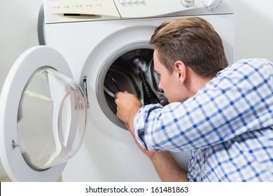 Side view of a technician repairing a washing machine