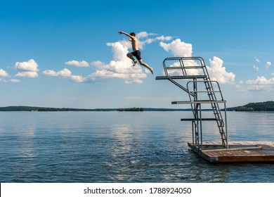 Side view of a teenage male jump diving from a diving tower with blue sky and horizon in the background.