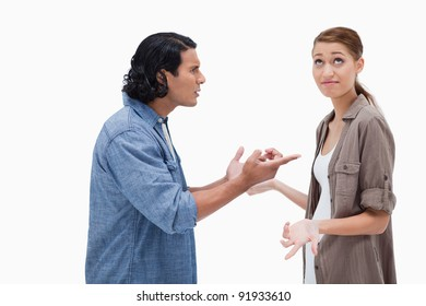 Side view of tensed talking couple against a white background