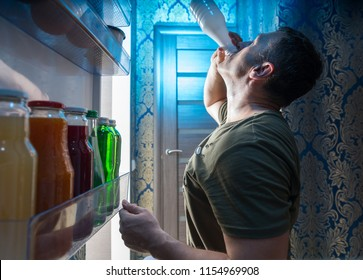 Side view of a thirsty man with eating disorders drinking yogurt in front of the fridge in the middle of the night