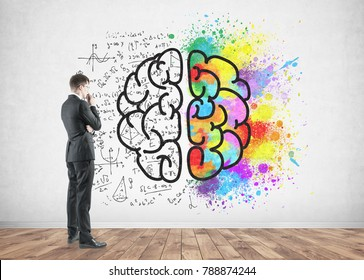Side view of a thoughtful blond businessman wearing a suit and thinking. He is looking at a colorful brain sketch drawn on a concrete wall.
