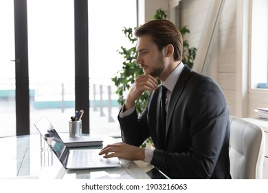 Side view thoughtful businessman looking at laptop screen, pondering task, online project strategy or financial report, pensive entrepreneur touching chin, using computer, sitting at desk in office