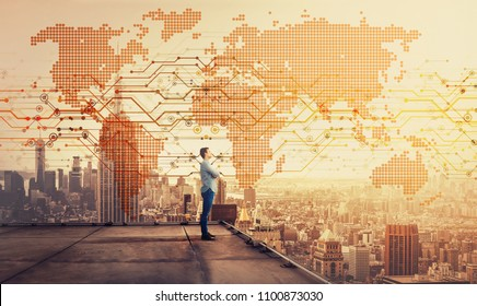 Side view of a thoughtful businessman standing on the rooftop of a skyscraper looking over the big city at sunset with a world map hologram projection. Cryptocurrency concept. Double exposure.